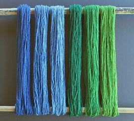 Skeins of yarn dyed shades of blue and green with indigo and natural dyes