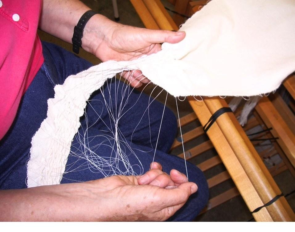 Weft threads being pulled up to gather fabric.